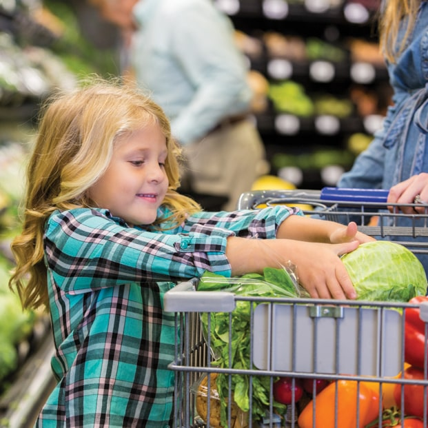 Child putting vegetables in grocery cart
